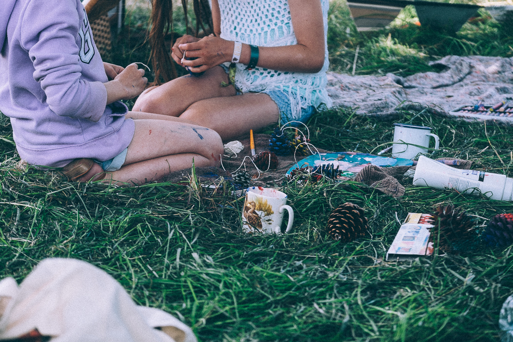 Girls crafting with pine cones at Camp Bestival
