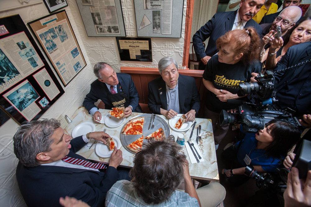 "NYC Mayor Bloomberg, Brooklyn Borough President Marty Markowitz, and Totonno's co-owner and lead devotee Louise ""Cookie"" Ciminieri, along with a crowd from the press."