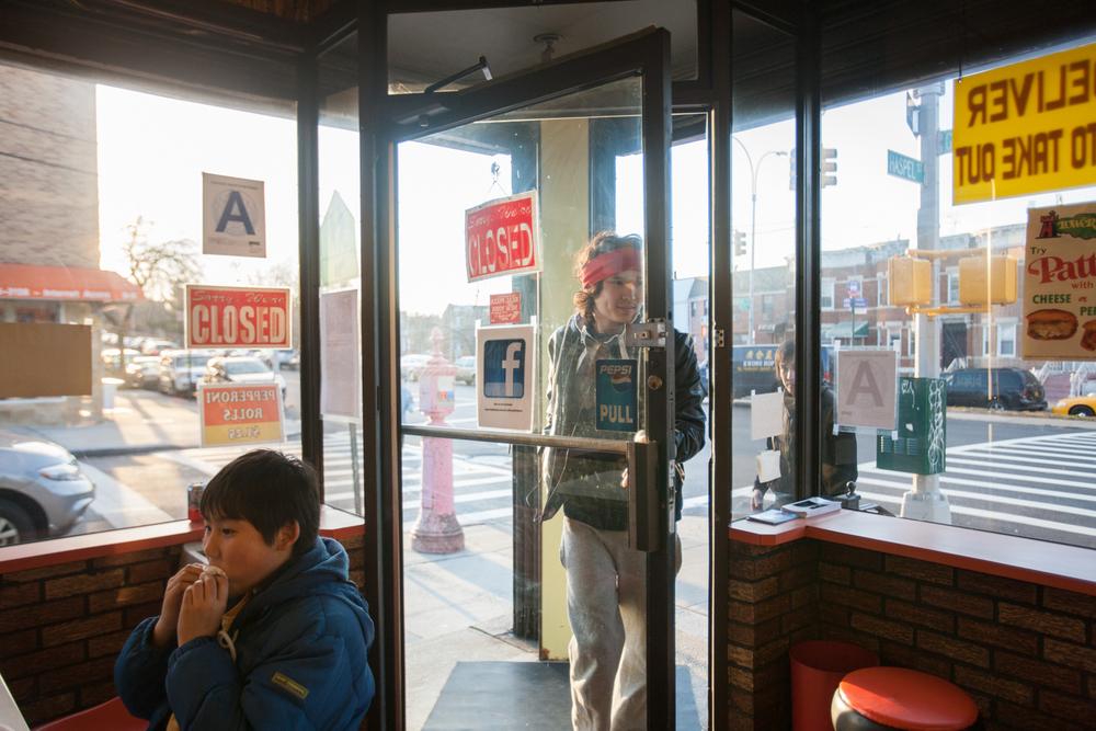 A customer entering John's Pizza, in Elmhurst, Queens