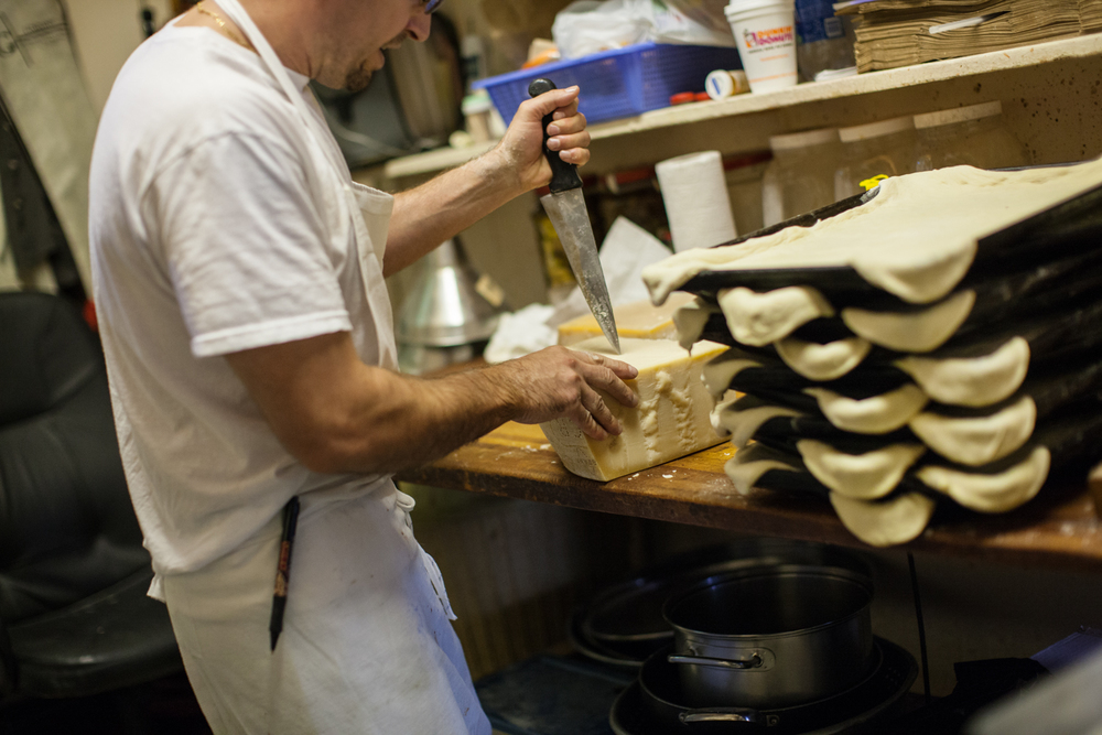 Di Fara Pizza is a family affair. Here, one of Dom's son's chisels apart a hunk of cheese, while square pies with stretched dough rest in the foreground.