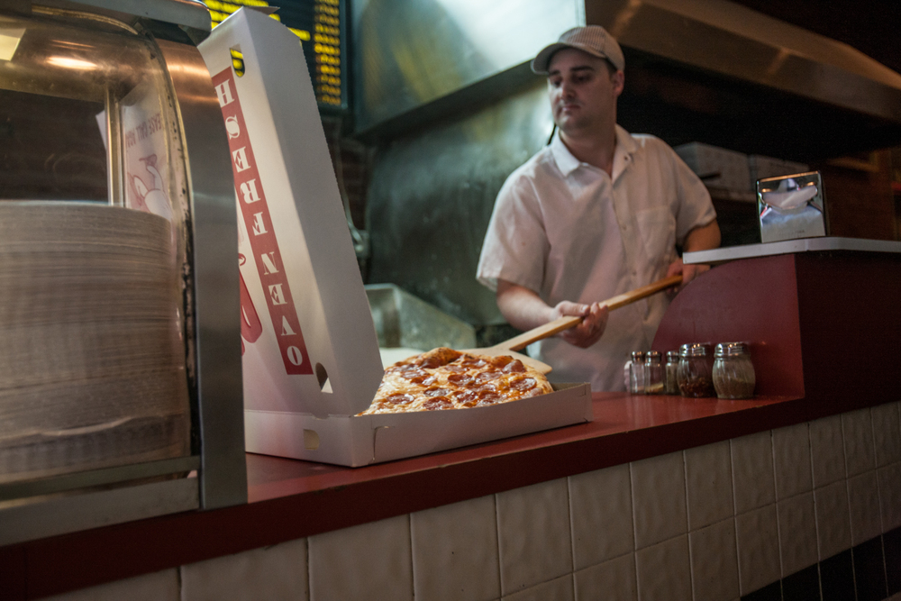 Sal & Carmine's owner Luciano Gaudiosi, slides a steaming pepperoni pie into a box.