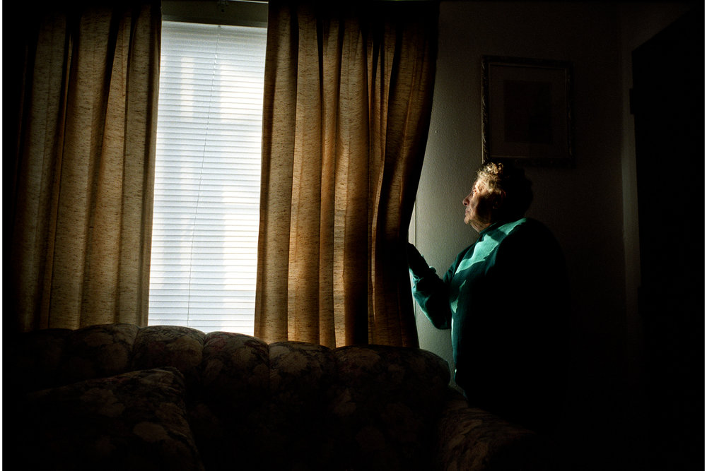 Eldery Woman Pulls Back Curtains to Look Out Window