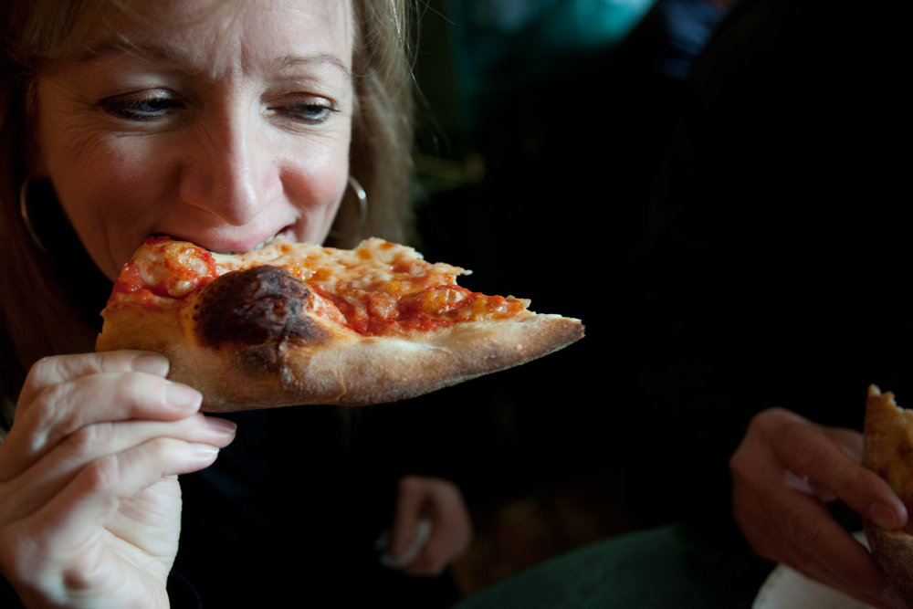 A customer eating a slice at Joe's Pizza, on Carmine Street, in the Village.