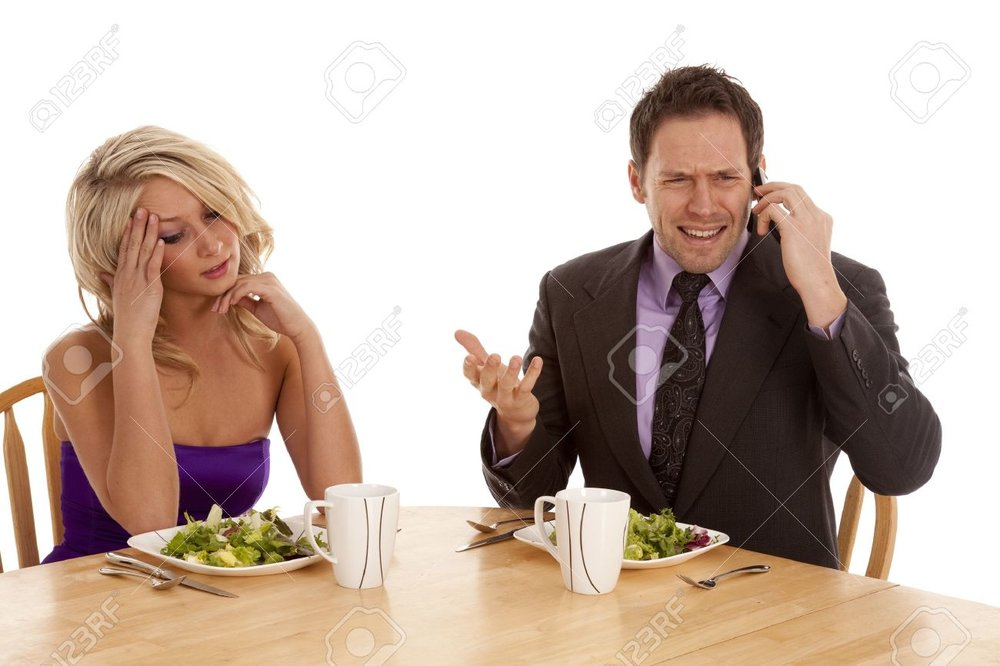 9321067-a-woman-sitting-and-being-frustrated-with-her-man-because-he-is-on-the-phone-while-they-are-having-a-Stock-Photo.jpg