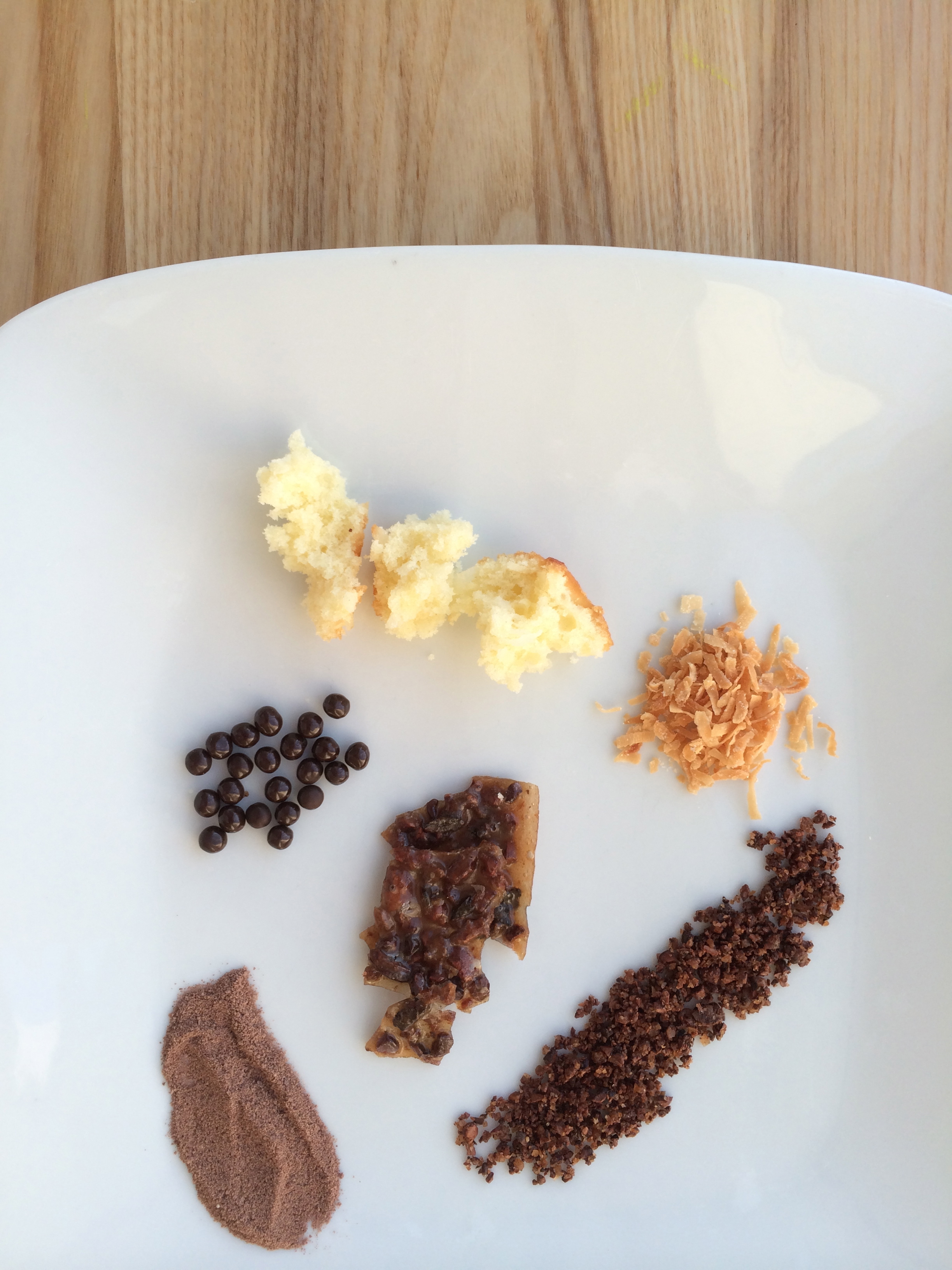 Here are the components on a separate plate. It consists of coconut cake, toasted coconut, chocolate pearls, chocolate cake crumbs, and cocoa nib crumble. I also added the cocoa nib crumble in its original state, a tuile.
