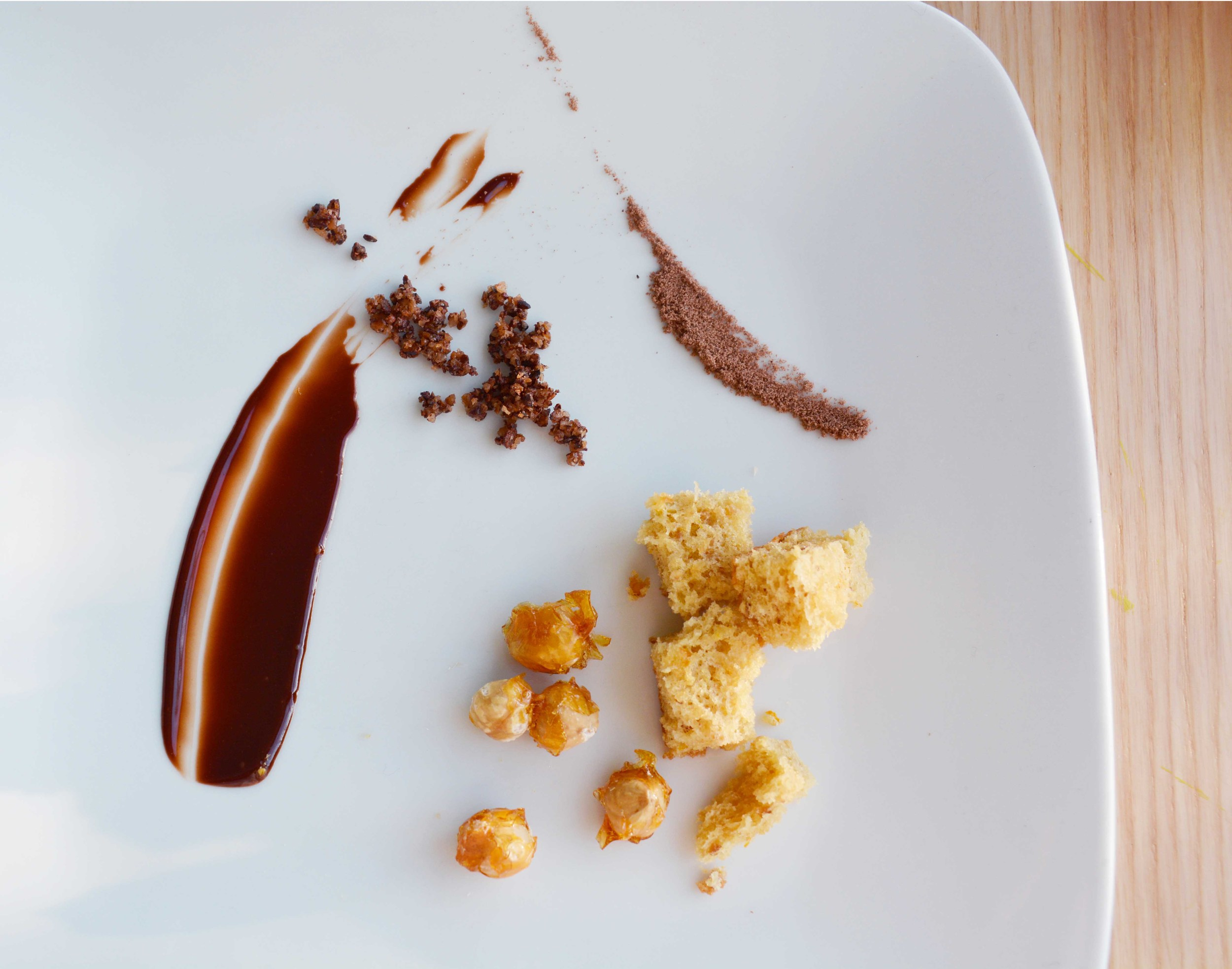 Some mise en place. Chocolate sauce, cocoa nib crumble, chocolate crumbs, hazelnut cake, and caramelized hazelnuts.