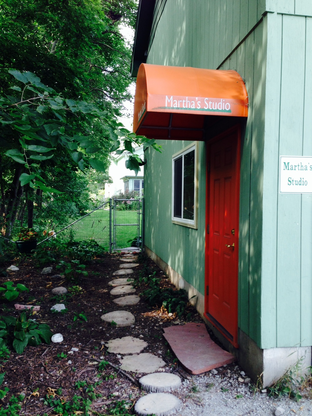 West entrance, off of the alley (first left turn south of Woodlawn Avenue.  Enter the orange door.