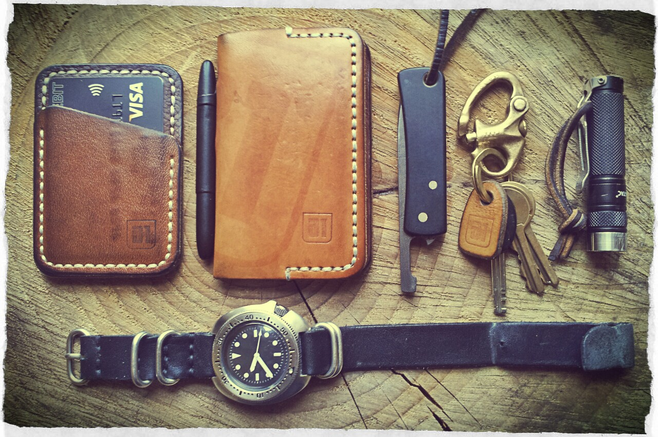 31trum :     Current pocket dump    Speedwallet (with sewn in Oyster Card   Mini Moleskine Cover and Spacepen   Michael Morris Friction Folder   Old brass Snapshackle   EagleTac D25A mini   Fully modded Seiko 6105 on handmade leather diver strap