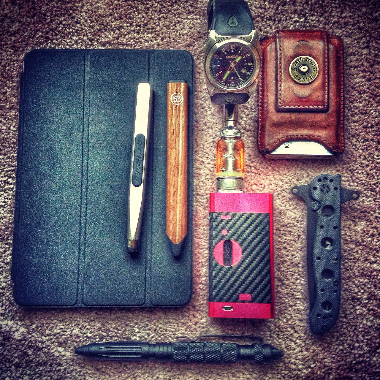 "pixeledthoughts: A pic of the stuff I carry with me everyday. iPad mini with Smart Cover , Pencil by 53 and Maglus,CRKT m16 knife, Uzi tactical pen, Cana mod with aspire nautilus , Nixon ""The Key"" watch, and Wallet. http://www.dailycarry.co"
