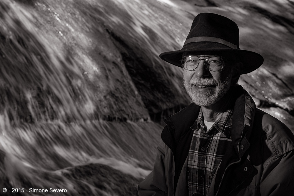 Don and I started talking in a photography meeting we had by Helen Hunt Falls. I think we had about 20 people in that morning and he was one of the new members I had not yet met. I asked him if he had heard about A Portrait a Day and he said not. I told him that he had been selected to be my subject, if he accepted. He said yes. The group hiked for about half an hour together until I found the falls that would fit m idea. He looks like the stereotype of the mountain man, an outdoor person who enjoys Colorado. The plaid shirt, the hat, the glasses and the coat. It screams Colorado hiker in my vision. He agreed to being in the image by the water. I set my camera on tripod with a slow shutter speed to capture the motion of the water. I had my boyfriend hold a coat to block light from the sun on his jacket. I asked my boyfriend's brother to hold the flash in front of John's face. We took 2 or 3 shots until I got it right - needed to adjust the power of the flash.