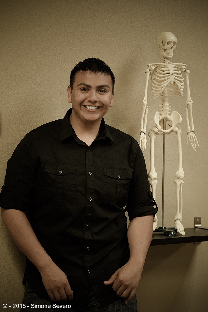 Sylvester is a massage therapist and he has this big young smile in his face all the time. I saw the skeleton in his office and I thought it would be really cool to have an image of him looking serious  by the bones, but instead he thought it was funny and gave me the big smile. I did take another picture where he and the skeleton are hugging but I liked this better. His portrait was made with the office light from the ceiling only. I did not have any flashes with me this day. I just bumped the high ISO in camera to ISO 2500. I desaturated the image to my taste.