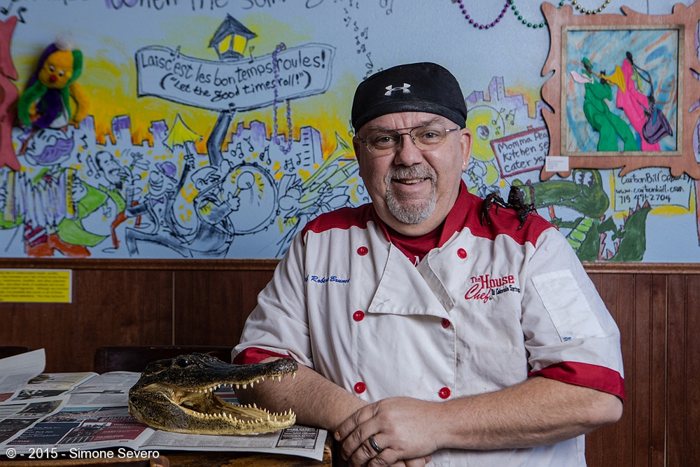 I met Chef BB the first time I went to his restaurant,  Momma Pearl's Cajun Kitchen . He was there, preparing crawfish the Louisiana way. We loved his food and I invited him for being the Portrait of the day. Three weeks later, I called him to confirm and he said yes. I arrived just in time to see Fedex delivering the live crawfish, including the one on his shoulder. The alligator was already there. While he started the preparation for cooking the crawfish I set up a mini studio inside his restaurant. My sweetheart Mike helped to prepare the tables. Chef BB was so nice and informed us he had been voted Best of the Springs Second Place, which is awesome for a small business. Everybody inside the restaurant applauded. He deserves it.