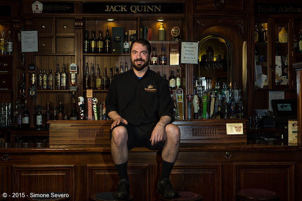 My dream is to go to Ireland...Jack Quinn's bar is the closest to that country for now, a very nice place to eat good foos have a friendly service and feel home in many ways. I mean, have you eaten there? The Irish food is amazing!! I am a huge fan of potatoes and when I go there I always order breakfast with egg and potatoes. This is Charles, the friendly guy who serves me when I am there. About a month ago I looked at the place and it reminded me of a picture I had seen in a magazine of a man seated in some shelf, but not a bar. Jack Quinn's being so unique with the old cabinets brought back to my memory the idea of photographing somebody in the bar environment, more like the kind of picture you would find illustrating a magazine. I asked him if he would be a volunteer for my project and he said yes. We scheduled 3 weeks out.  I first thought of using one light only, but I ended changing my mind and I used 3 flashes instead. I wanted to keep the war atmosphere of the bar, so I used a filter CTO in all flashes. There is one flash with a softbox to his right, one in front of him and one behind him - pointing to the cabinets.  He shared he is a huge fun of baseball, he had not posed for a picture since high school and he had just been back from vacation in Las Vegas (which is why we scheduled this date, so he would be back for the picture). He seemed to have fun watching me setting up the lights and testing them until we were ready to place him in the spot of the picture. He was  serious in the first one but then he said he wanted one smiling and this ended up being the one I chose.