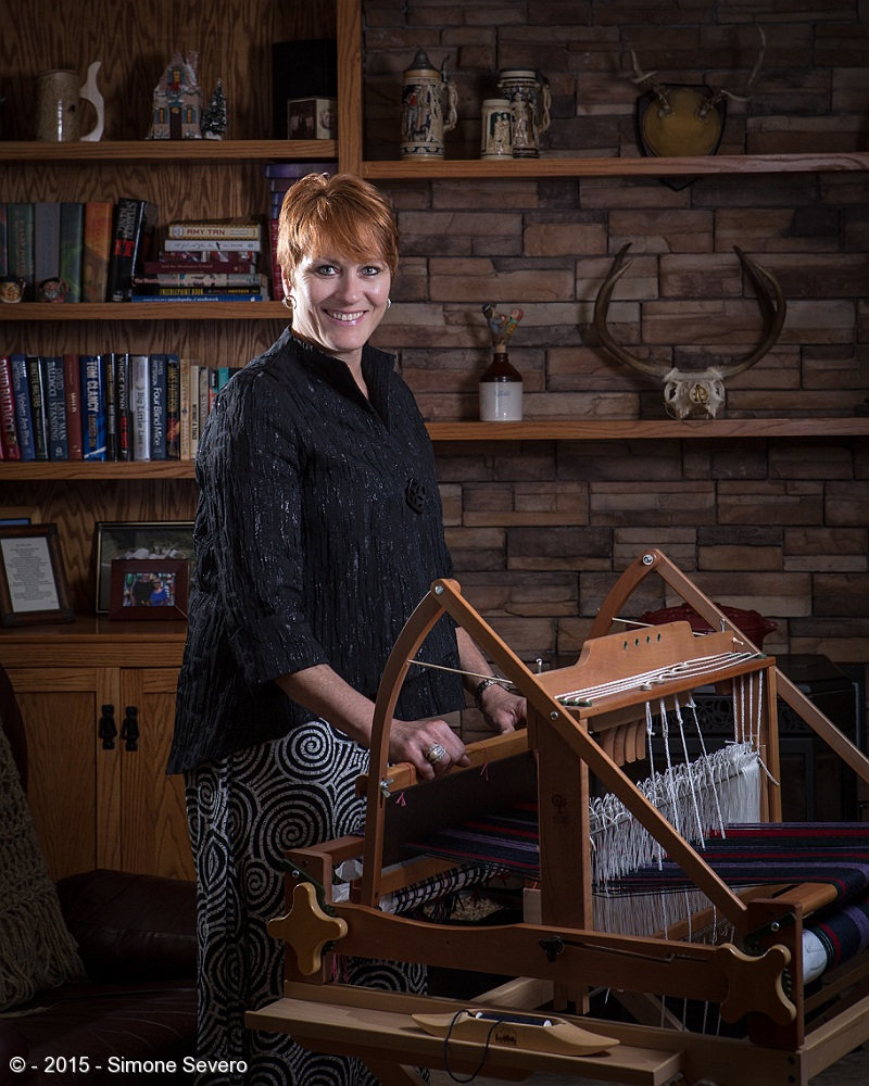 Heather is a very active person. We talked about taking pictures while she is biking - she loves long bike rides - but she decided she wanted a portrait with her creative outlet of weaving.   She had just been in a craft show for 2 days with some friends and she was inspired by the energy of the event. The weaving machine, she told me, is set up for weaving while you are sitted, but we wanted to portrait her with the machine so we decided to get her standing by it. The original idea was to do the portrait outdoors but this room had so much character and personality I could not pass the opportunity. Two flashes were used for this image. One was a bare flash to lit her hair and one speedlight with a softbox.   She loves the bikes and the oudoors life. She told me blackforest fire barely spared her house: I saw trees within 30 feet of her house completely burned. They lost the shed, but the house was saved. It made her re-think of how materialistic our society is and how easy it is to just accumulate things you don't need. She was really grateful for still having her home with all the memories it holds.