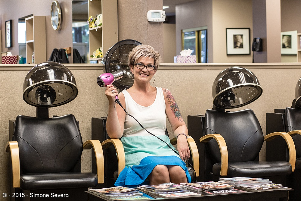 Rebecca has been a hair stylist for about 20 years. She has been taking care of my hair for over 3. Every six or 8 weeks I go see here. She used to come from Gunnison every two weeks to attend her loyal clients but she moved back to Colorado Springs last year. I have seen her engage with clients and pick up the conversation where it was left 6 weeks before: it happens that the day I go the other regulars go there as well on the same schedule as I do my hair - every 6 or 8 weeks - so I got used to some faces and stories I hear while waiting my turn. She knows my friend Carmela who moved to Arizona last year so we talked about how much we both miss her.   I wanted to take a picture being right in front of her, showing the 5 drying stations, but I grabbed the wrong fixed lens before leaving the house so I needed to compromise and change my angle to make it fit in the space I had to work with.  This time I did not use flash, but a continuous light with 5100 degrees Kelvin, diffused by an umbrella.