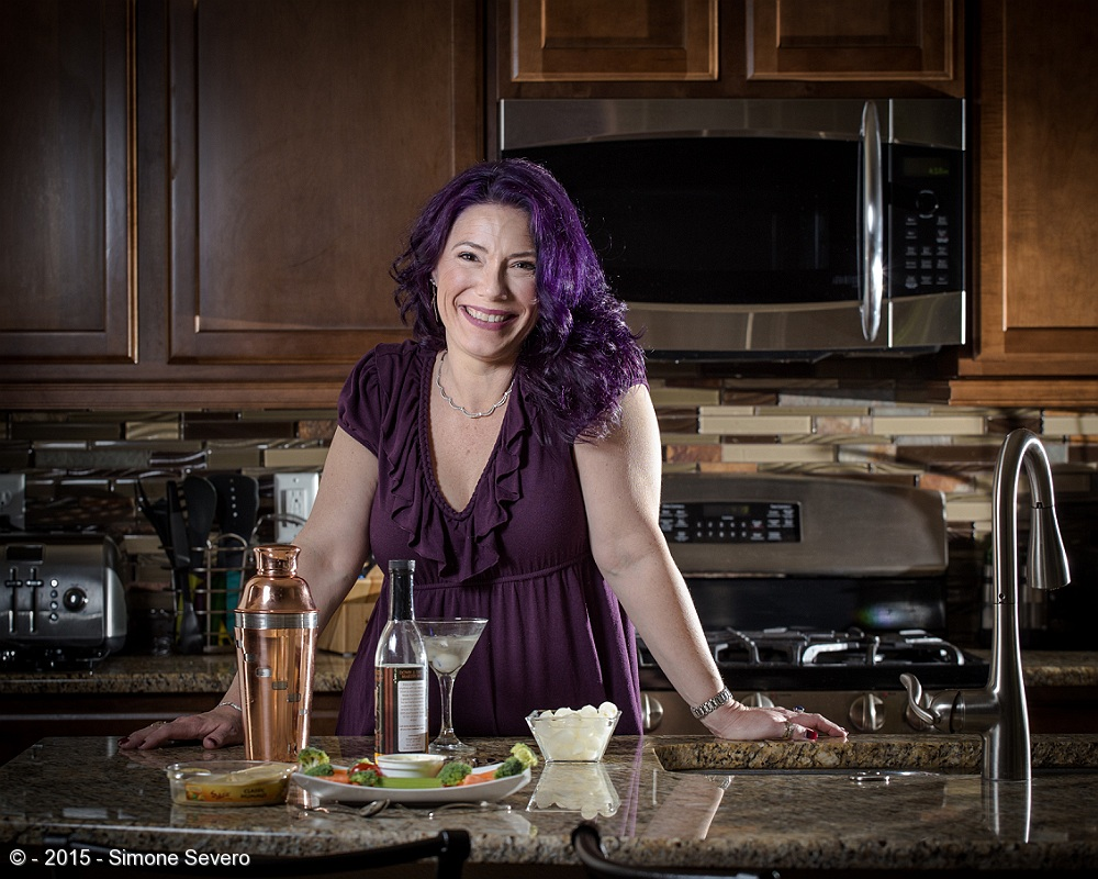 Mimi has a bubbly personality. We met once, for about five minutes and we scheduled her portrait right away. I knew nothing about her except she loves purple.   We ended up anticipating her portrait about 3 weeks earlier because I was lucky to have Fox News to pick the story of the interesting people I photograph to be featured on tv. Mimi said yes. We spoke on the phone and I explained I would like to capture her personality, alive and happy instead of a formal portrait.  I also love purple, so I knew it was going to be a good one because of her energy. There is something very special about her.  She is very emotional, honest, and beautiful. When I asked her about what she liked doing she told me she did not have any hobby but she does an awesome martini and her grandmother taught her how to do it. We picked our theme.   According to her grandmother, who now lives in Heaven, when it is five o'clock it is time for a Martini, and it is always five o'clock somewhere. She learned how to make martinis and she has very fond memories about her grandmother, who is a big inspiration in her life. So that is the story of how she made me the first martini I ever had. I learned I like martinis.   This was a very high energy, emotional session, one that brought beautiful and powerful memories and made us connect more.  She will have a portrait that is meaningful to her and I just made a new friend. Another wonderful day. 221 more to go!!