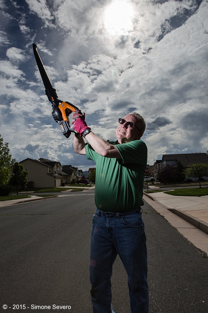 Bruce is my neighbor. He always decorates for the Holidays but today I found him and his wife Dar(lene) doing yard work. I stopped by  to check how they were doing and asked him if he could be my portrait of the day.  I wanted his portrait to have an association with the chain saw movie because I thought it was funny he had a wind blower for leaves that reminded me of the movie. I asked him to raise it against the sky. there was one flash without any modifier about 4 to 5 feet away to the left. He loves gardening, enjoys every holiday all year round and enjoys the company of his wife and dog.
