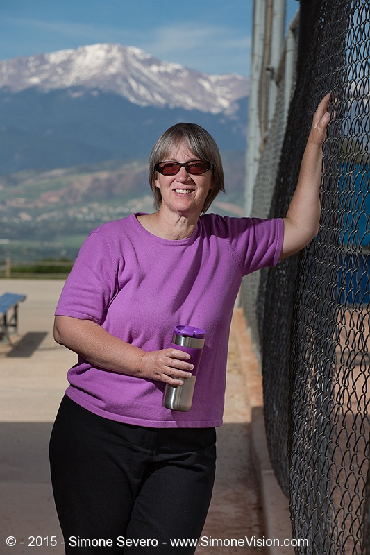 Mary worked all night until 8 am and went directly to meet me at the park for her portrait. She had a cup of coffee that matched her shirt so I thought it was really unique that she matched it.  We first did one portrait of her with her cup of coffee in the bleachers, which turned out really well, but then we went inside the baseball dugout and she loved having the mountains on the back. She said she was on a matching day, so the three things she could share she loved so much start with C: Cameras, Computers, and Coffee.  After her portrait, Mary and I took pictures of Sandy,  with her dog. Sandy was my portrait on June 10. She joined us today so we could photograph her with her white dog. We spent a great time together until about 10:30 in the morning, when we left to celebrate Father's day.