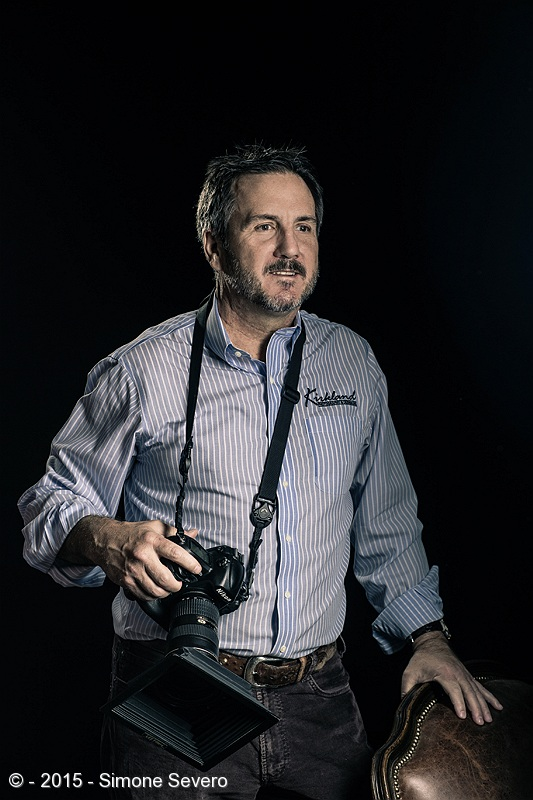 "I met Mark 10 years ago. He is one of the best photographers I know. He has a studio in Palmer Lake where you can see his enthusiasm about documenting people's lives.   Mark's life is about photography. At least the side of Mark I get to see. He has very little time for himself so I was very happy when he accepted my invitation to be my portrait of the day.  I know him as a friend and amazing photographer but above all Mark is a people person who connects and engages with every person he meets.  When I first met him, he was a wildlife photographer and he had just been awarded in an international contest.  Throughout the years Mark continued to improve as a photographer.  He praises God and he is a man of faith. He feels the blessings that shine on him as an act of God's will but he deserves every single one of them.  My best friend Tara was with me when I created his portrait in his studio. Funny how I remember...Mark sets the lights, and grab his camera and ask me about light ratio and hair light and...""no,no,no...that is how YOU light.  Turn that off, turn that off and move this one"". Now I arrive in his studio. It took a little of playing to adapt to his wider studio. I f the light was not the way I had in mind, my post processing would not match the way I had in mind.   I wanted a portrait that was a mix of a serious portrait (but not too serious) and a hint of a vintage look. A beautiful portrait of a nice gentleman."