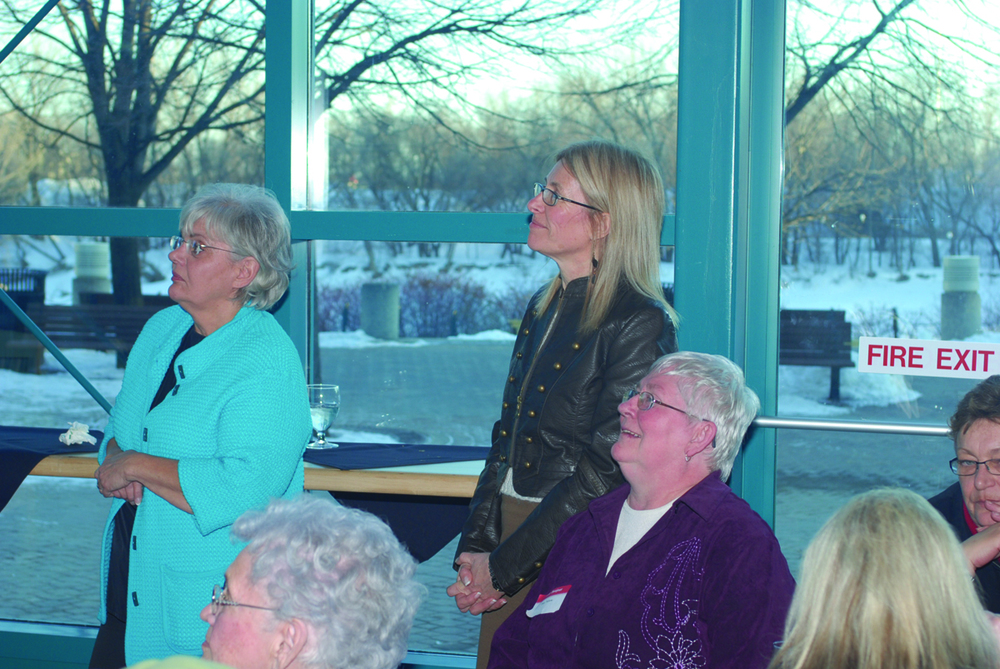 Picture of Angela Stratity, Bonnie Heath, and Sue Tebow – all three are looking to the Left at something not visible in the picture. Angela Stratiy and Bonnie Heath are standing while Sue Tebow is seated.  The picture is at the Forks Market atrium, and you can see a 'fire exit' sticker on the window and it is winter time, dusk. (ECCOE's 30th Anniversary.