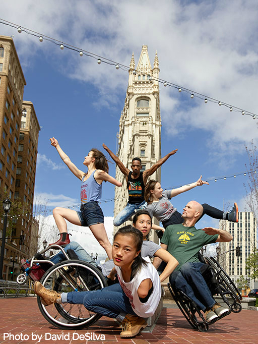 A sunny day at Latham Square in Downtown Oakland. Six AXIS Dancers perform with a tall, skinny building in the background. Dancers Julie Crothers, James Bowen, and Liv Schaffer leap in the background. Carina Ho dances in front of them, leaning back in her wheelchair with her feet in the air. Dwayne Scheuneman is beside her. He manipulates his chair to tilt at an angle with one wheel off the ground, his left arm up at a sharp angle. Dancer Lani Dickinson kneels in front of them with one leg extended to her right and her body leaning toward the camera. Photo by DavidDeSilva