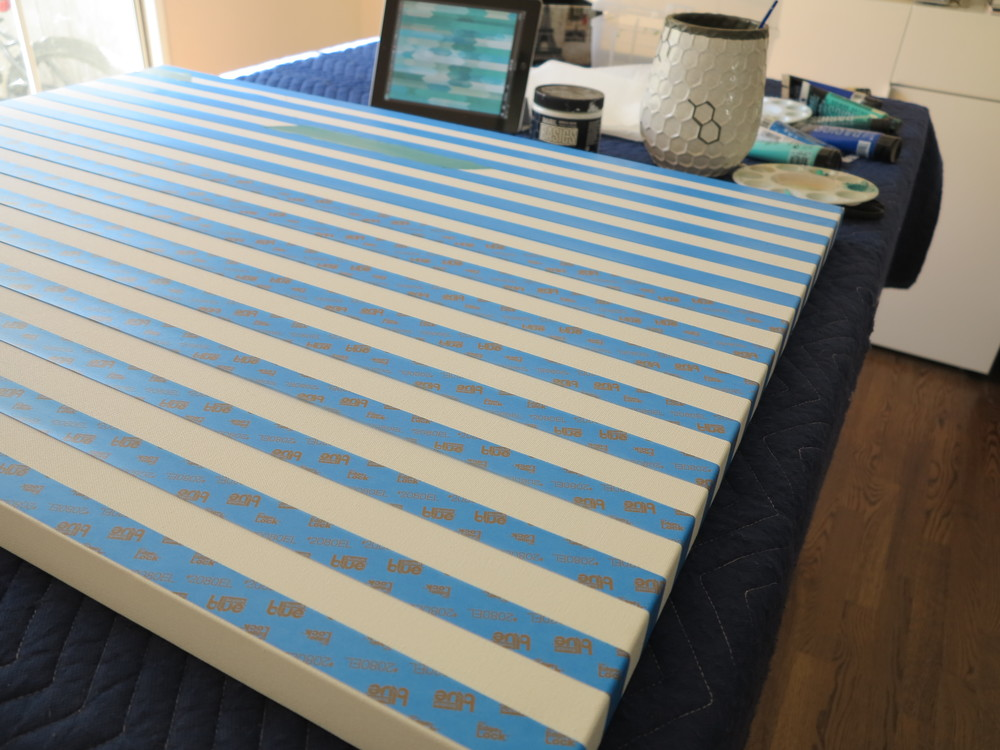 I was inspired by a graphic design I saw online and used it as my guide.  I stretched blue painters tape across the length of the canvas making sure it wrapped around the sides and equally spaced it out by it's own height.
