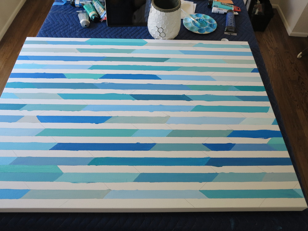 I peeled back the tape to reveal the unpainted rows of canvas.  I maticulously painted the blank sections with a thin paint brush.  I didn't have taped lines to ensure a straight edge so this part was particularly time consuming as it took a very steady hand.  I was also 7 months pregnant and couldn't bend over for long periods of time!