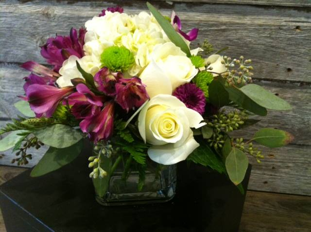 Roses, hydrangea, alstromeria and orchids in a cube