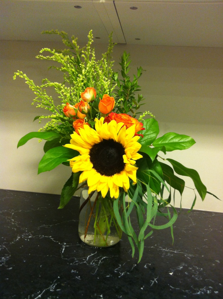 Sunflowers and orange roses in a mason jar
