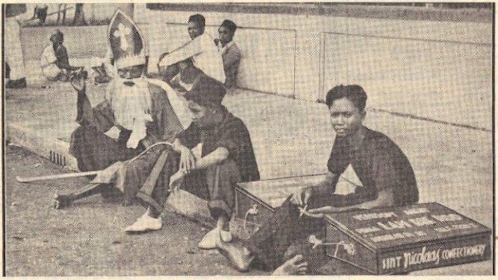 Sinterklaas (dari bhs Belanda atau Sint Nicolass, Inggris : Saint Nicholaus. Beda dengan Santa Claus)) sedang nongkrong di pinggir jalan Surabaya. 1938. Untuk penjelasan tambahan baca di  https://www.facebook.com/didotklasta.harimurti/posts/10205420538368750