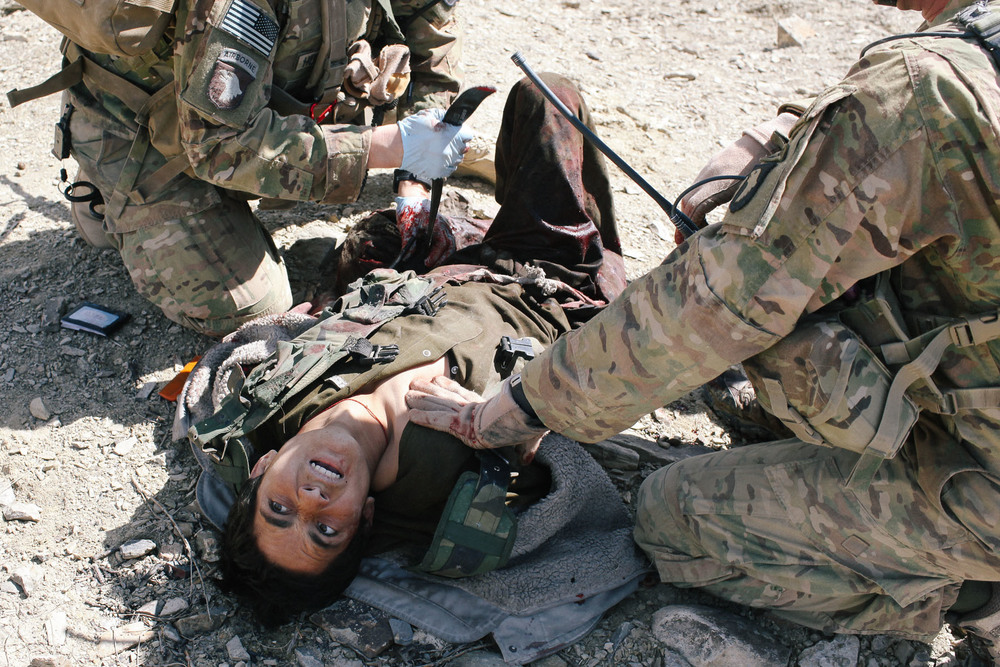 A medic works to stabilize a youth who was shot while attacking a fortified US outpost with an AK-47 and a pistol. He was airlifted to a larger base on order to receive advanced medical care.