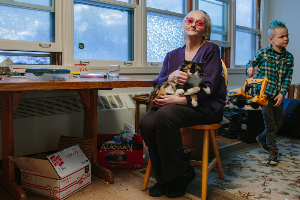 Terry Bender sits in her daughter Brandi's apartment petting the family cat, Willow. Terry also lives in an apartment in the building. In the background is Terry's grandson, Chase who is the fourth generation of his family living in the Begich Tower. Terry's mother was known as the 'Matriarch of Whittier' in her day.