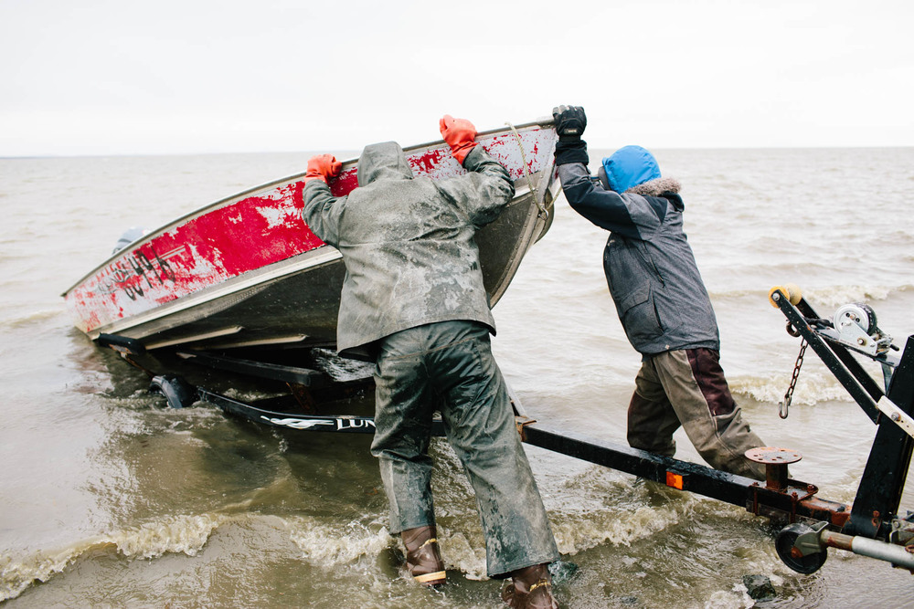 Peter Lockuk Jr. and Jim Logusak launch a boat into Togiak Bay on a mission to trade ivory and native crafts with a herring processing ship at anchor 8 miles away.