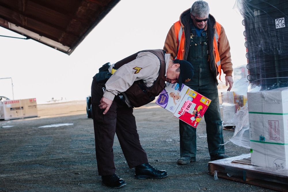 "Roger Wassilie, Togiak's Village Public Safety Officer, inspects incoming cargo for illegal alcohol. Togiak is one of many ""dry"" communities in which alcohol is illegal."