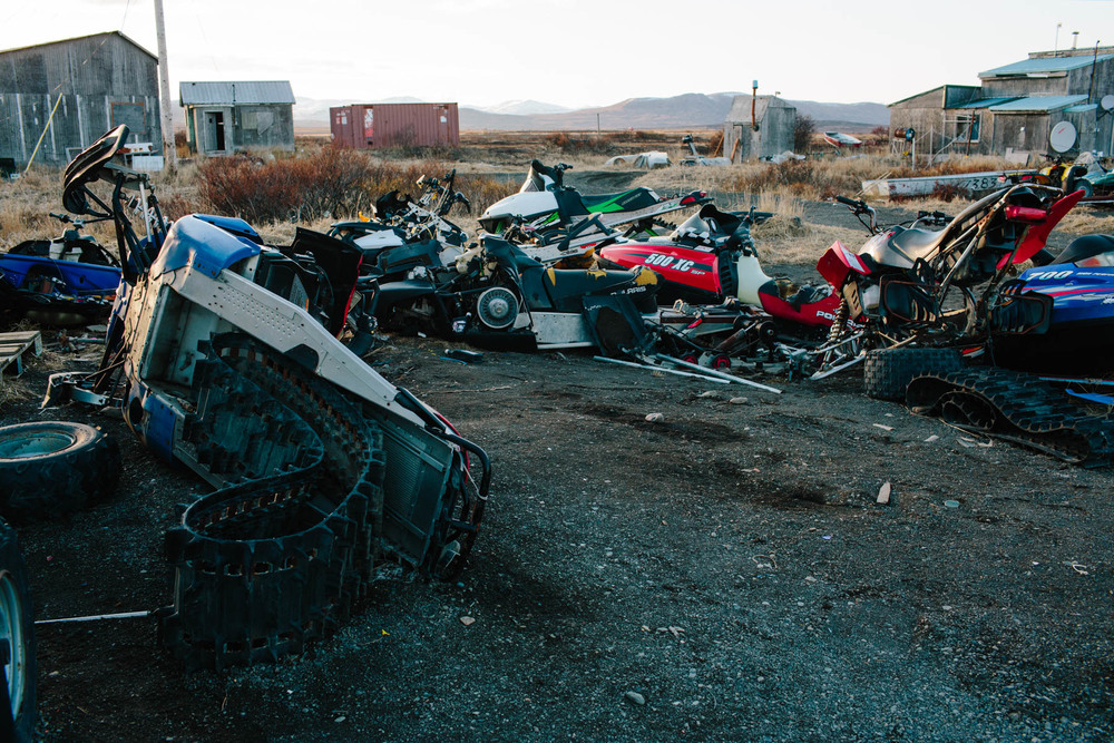 Remnants of broken down snowmobiles scavenged for parts lie in a heap.