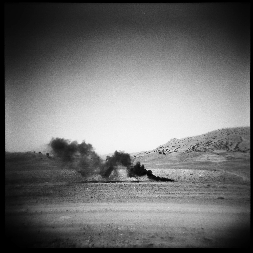 A smoke flare marks the landing zone for supplies to be dropped from a plane near FOB Tillman on the Af-Pak border of Gayan district, Paktika province. 2011.
