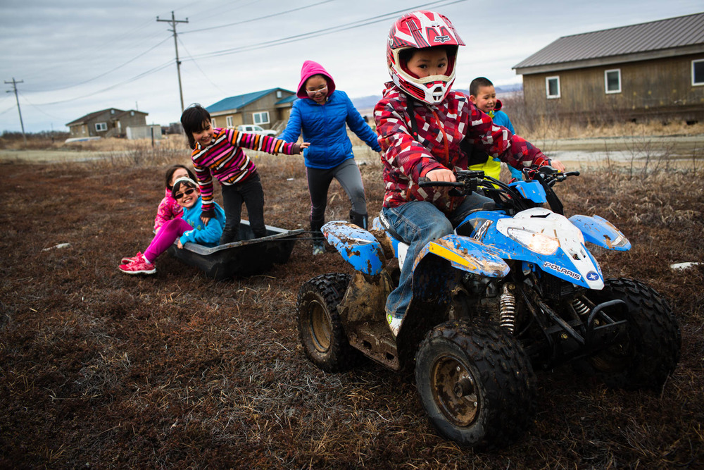 Without snow, the children of Togiak, Alaska have gotten creative with their sledding. Lloyd Kritz (wearing helmet), pulls Kiersley Kritz (left, hidden), and Brooke and Brea Wasillie through the mud behind a kid-sized ATV. Alyssa Coopchiak and Dreydan Coopchiak(r, background), watch.