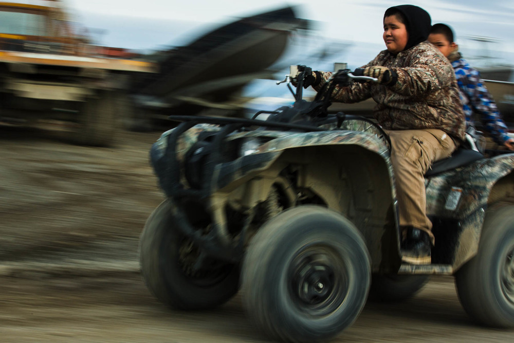 Kobe Pauk drives his  brother, Allen Pauk, through town on an ATV, the preferred method of summer transportation around Togiak, Alaska for young and old alike.