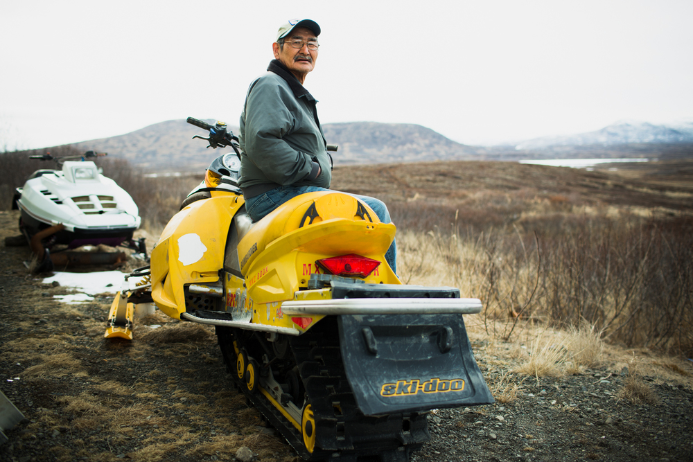 Frank Logusak sits on his son's snowmobile behind his home in Togiak Alaska on April 22, 2015. The past winter's limited snowfall made accessing hunting grounds more difficult for hunters in the community.
