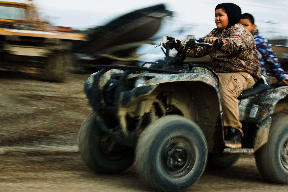 Kobe Pauk drives his  brother, Allen Pauk, through town on an ATV, the preferred method of summer transportation around Togiak, Alaska for young and old alike. Assignment for Newsweek.