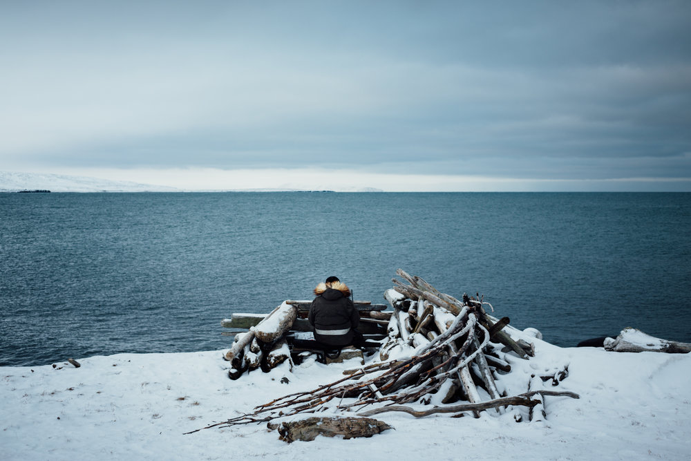 Derek Akeya sits in a hunting blind hunting for walrus or seal outside of Savoonga on St. Lawrence Island, Alaska.