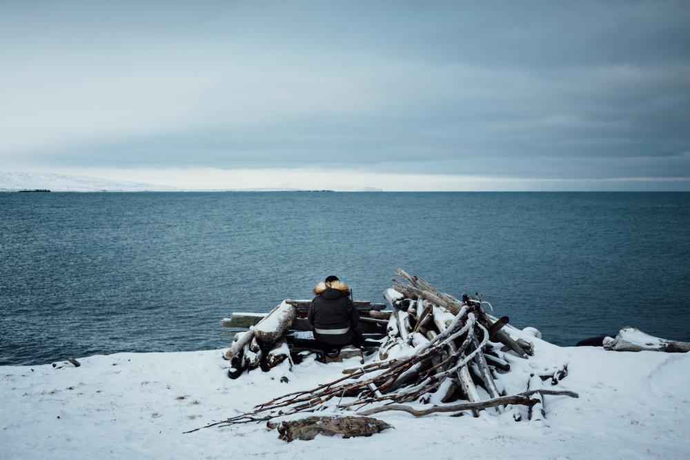 Derek Akeya sits in a hunting blind hunting for walrus or seal outside of Savoonga on St. Lawrence Island, Alaska.