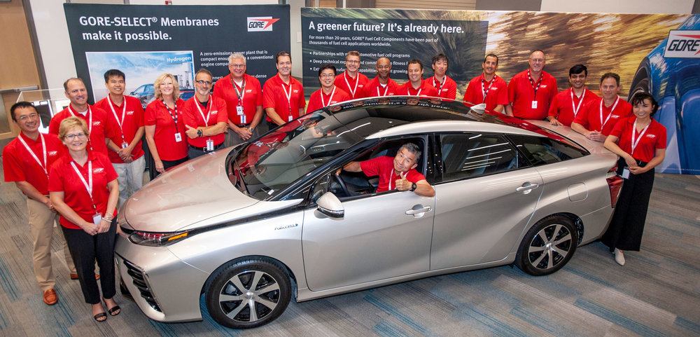 Gore associates gather around the zero-emission Toyota Mirai fuel cell vehicle at a recent auto industry event.