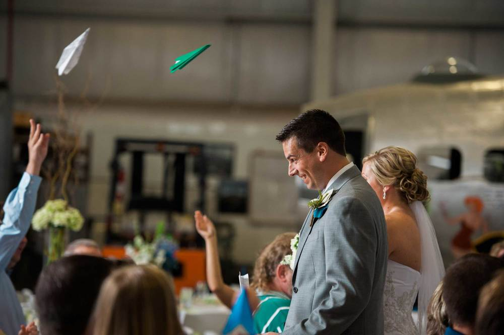 Paper airplanes being thrown for wedding ceremony at the Urbana Aviation Museum