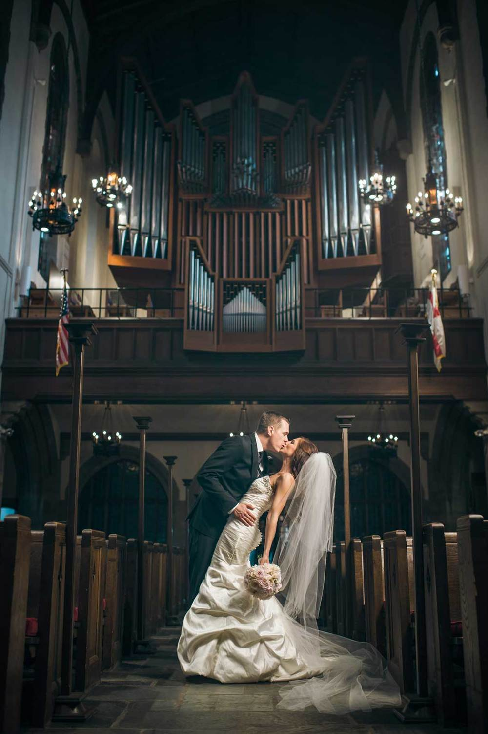 Bride and groom kiss in First Congregational Church in Columbus, OH