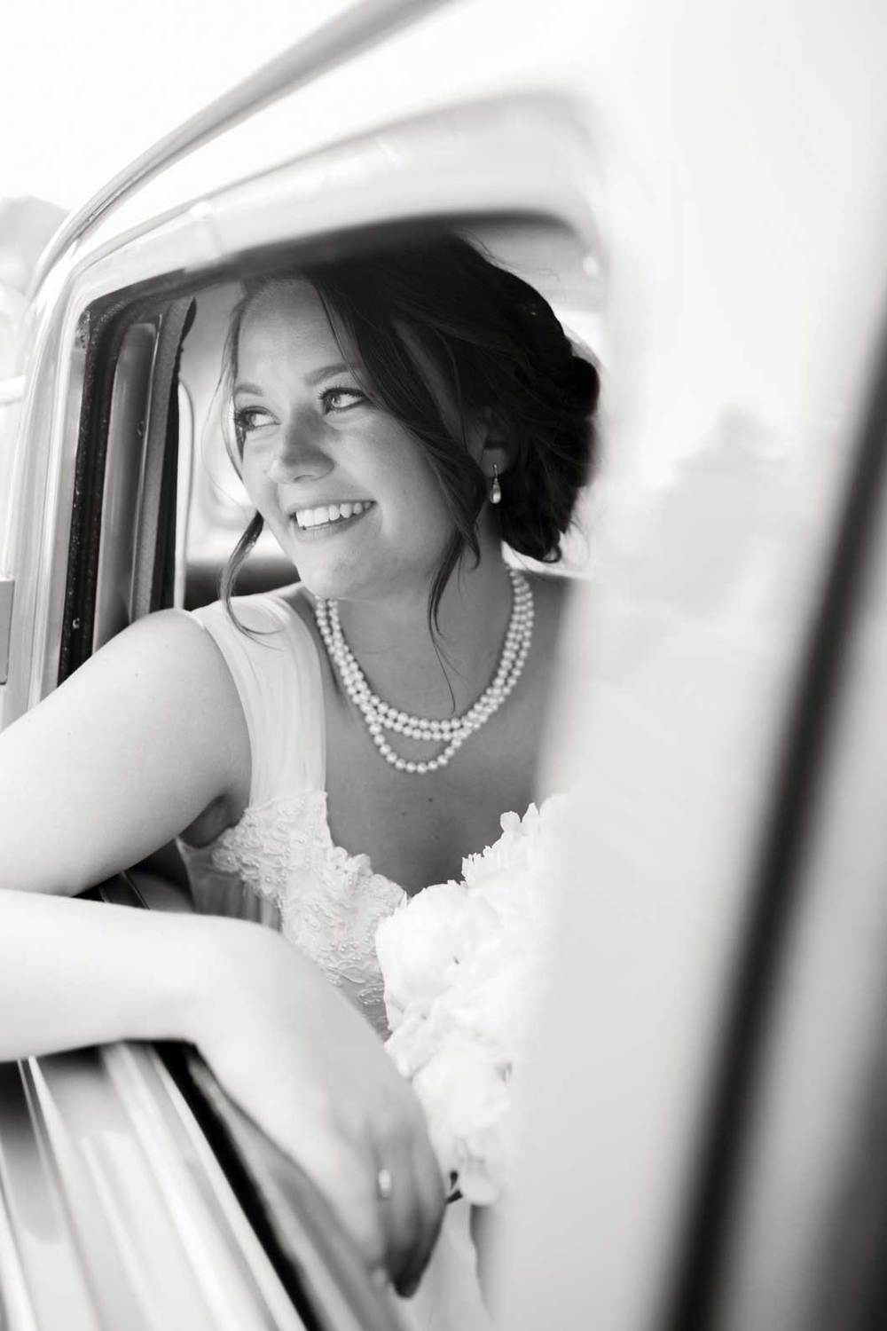 Bride sitting in her grandfather's vintage car