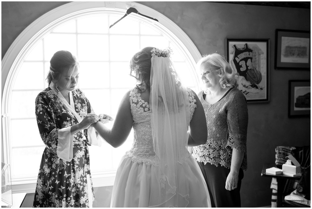 mother and sister help bride with jewelry