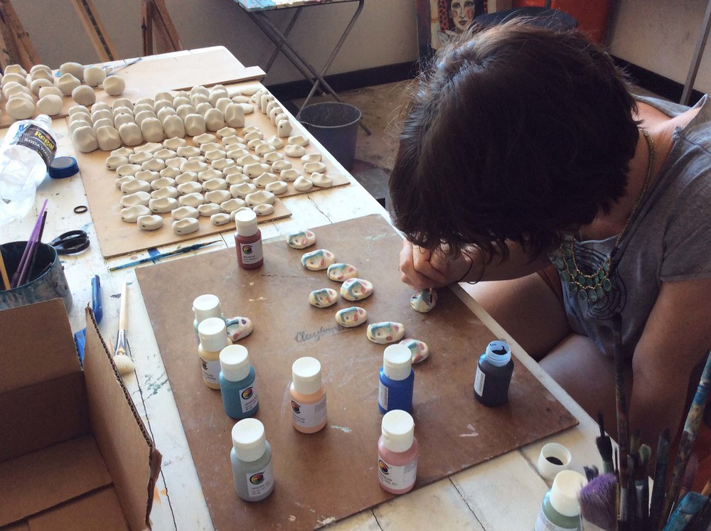 Ellie Hannon painting ceramic worry doll faces
