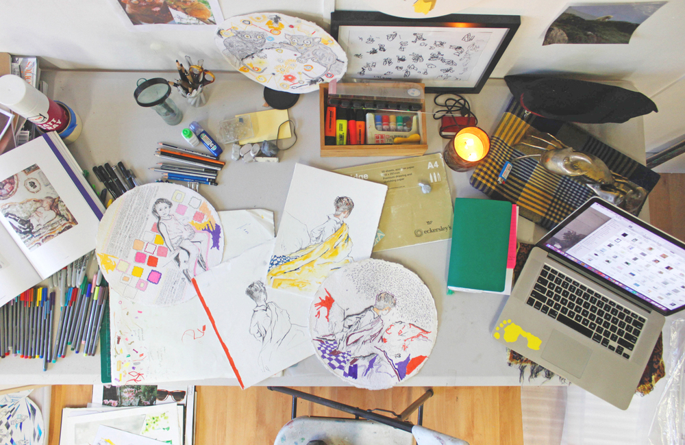 Kieth's desk with old and new drawings of the same subject, demonstrating the process.