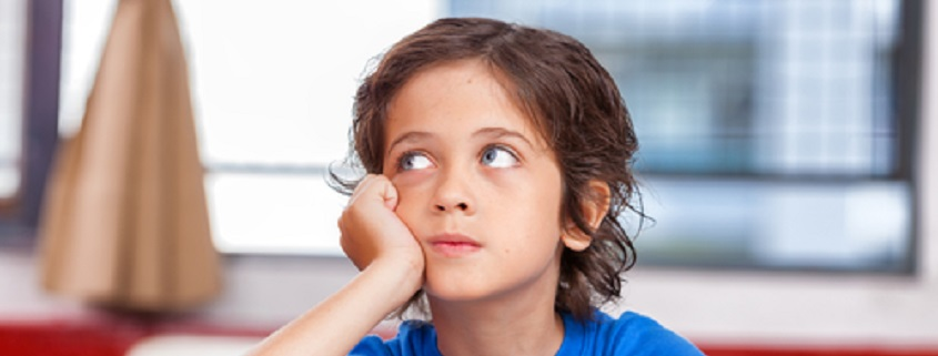 Primary school kid thinking about answer sitting at his desk